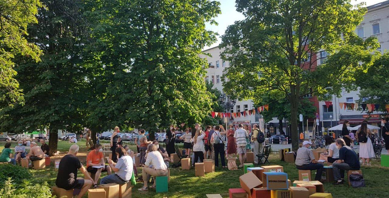 Menschen beim 3. Kiezgespräch auf dem Karl-August-Platz in Charlottenburg, Berlin.